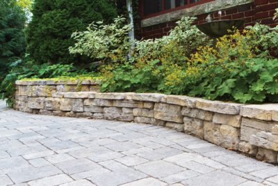 rock wall garden with paver patio area by Sutherland Landscape