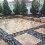 Sutherland Landscape natural rock retaining wall and stylish pavers create usable backyard space with stylish appeal