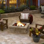 Sutherland Landscape stone paver patio and low retaining wall creates a planter area and fire pit
