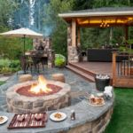 Sutherland Landscape backyard inspiration with deck, pavers for a patio area, fire pit and low retaining wall that serves as a seating area