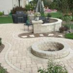 Sutherland Landscape backyard patio with pavers, low retaining wall to divide space, and a fire pit